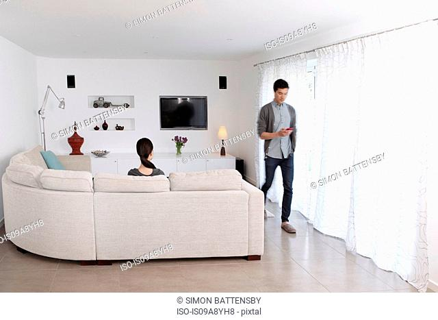 Woman looking at man walking away with mobile phone
