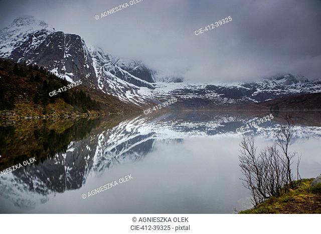 Reflection of snowy, rugged mountains in water, Storvatnet, Lofoten, Norway