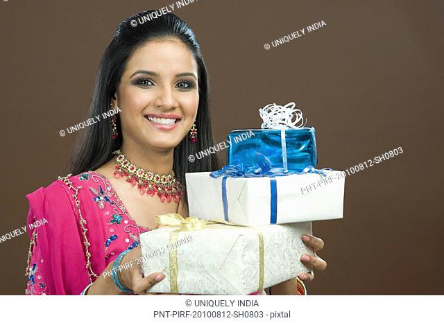 Portrait of a woman holding stack of gifts