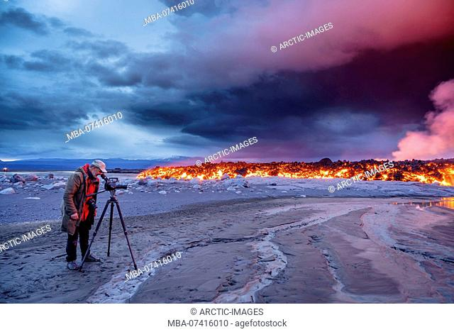 Photographer filming the volcano eruption at the Holuhraun Fissure, near the Bardarbunga Volcano, Iceland. August 29, 2014 a fissure eruption started in...
