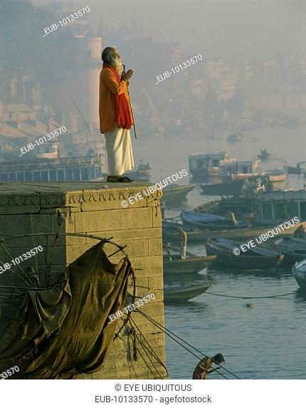 Holy man praying on stone wall above River Ganges with misty town and boats in background