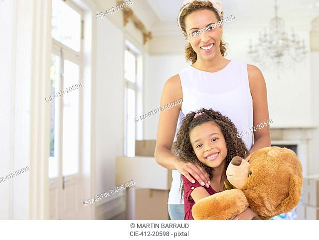 Mother and daughter smiling while clutching teddy bear