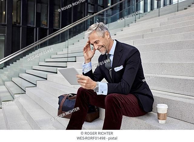 Fashionable businessman with travelling bag and coffee to go sitting on stairs using tablet