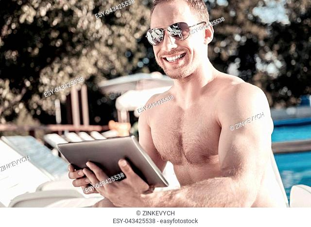 Positivity is the key to success. Sporty young man looking into the camera with a broad smile on his face while sitting on a sunbed with a tablet computer in...