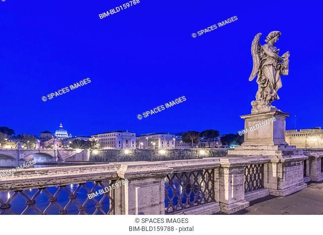 Statue over illuminated bridge at night, Rome, Italy