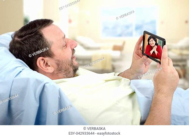 Bearded male patient lying on hospital bed has video chat with happy woman on smartphone. This hospital offers free wireless internet access Wi-Fi