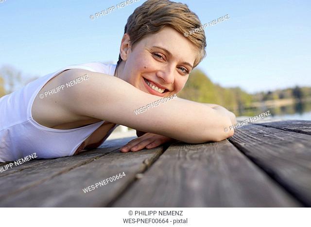Portrait of happy woman lying on jetty