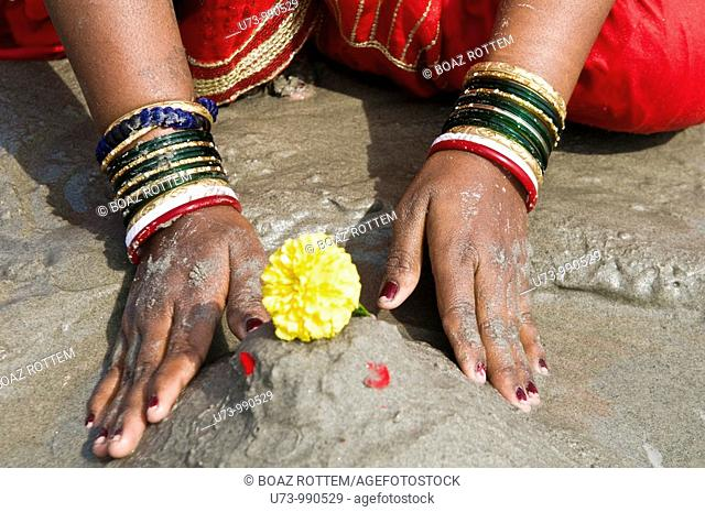 A woman performs a puja on the beach of Gangasagar island during the annual mela / festival which takes place on the island every January
