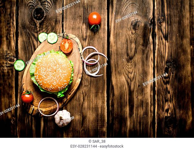 Cooked Burger with vegetables, cheese and meat. On wooden background. Top view
