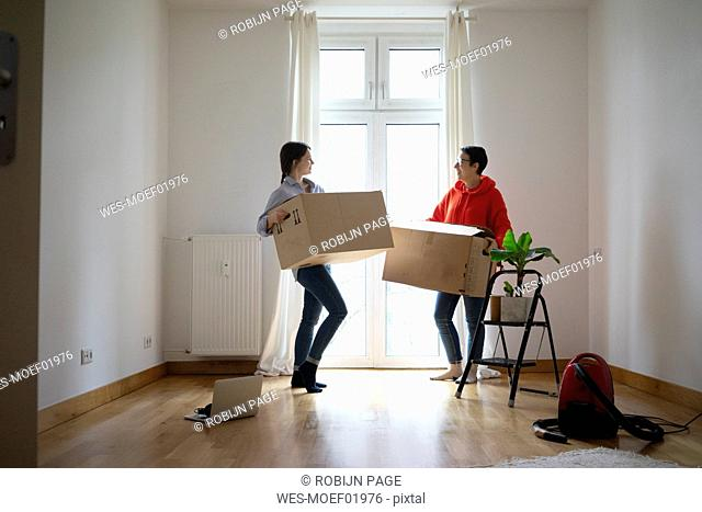 Young women moving into their new home, carrying cardboard boxes