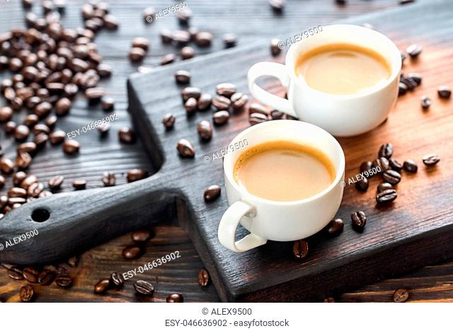 Two cups of coffee with coffee beans
