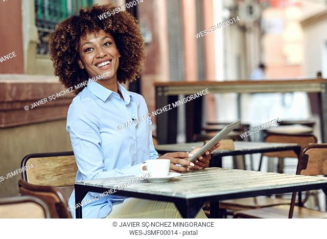 Smiling woman with afro hairstyle sitting in outdoor cafe with tablet