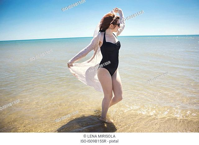 Young woman dancing in sea, Narbonne, France