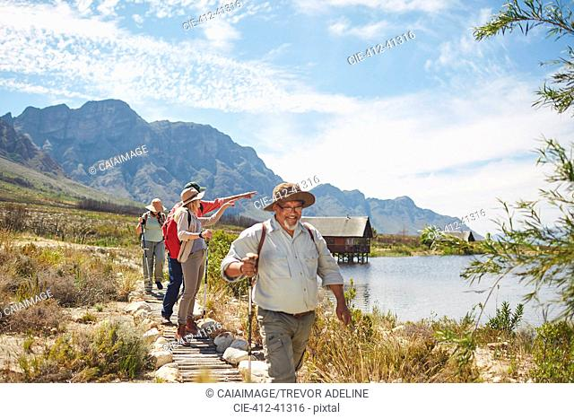 Active senior friends hiking and enjoying sunny summer lake view