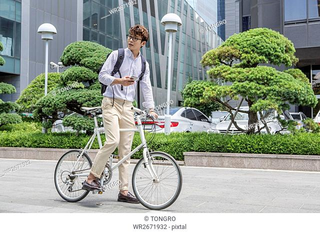 Businessman with smartphone and bicycle