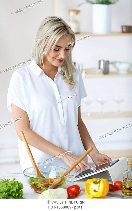 Smiling young woman using digital tablet while preparing salad at kitchen counter