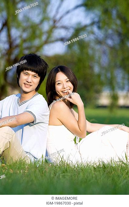 Young couple sitting on the lawn, back to back
