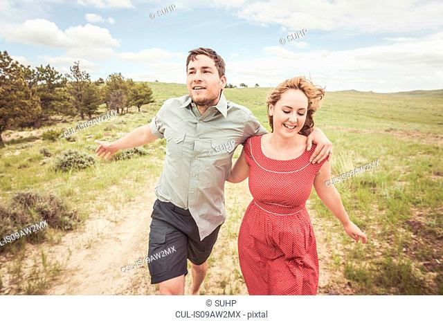 Young couple running on hilltop track, Cody, Wyoming, USA