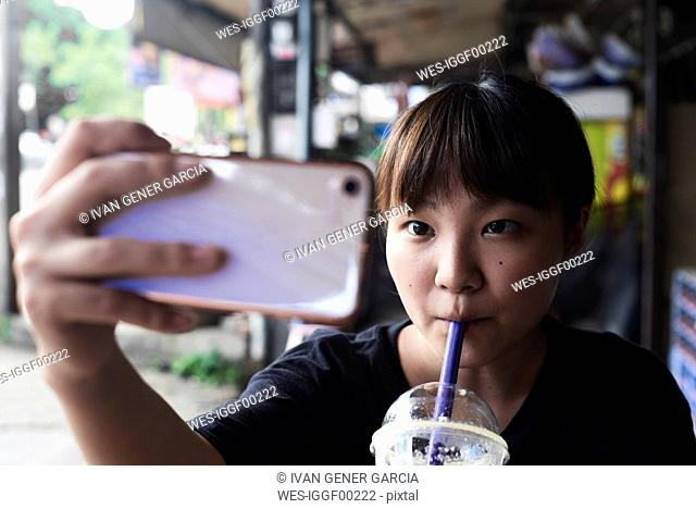 Portrait of woman drinking smoothie while taking selfie with smartphone