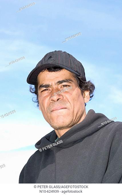 Young Hispanic man, wearing a hat, posing