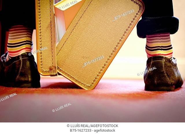 Old suitcase open with books in, between the legs of a man with striped socks