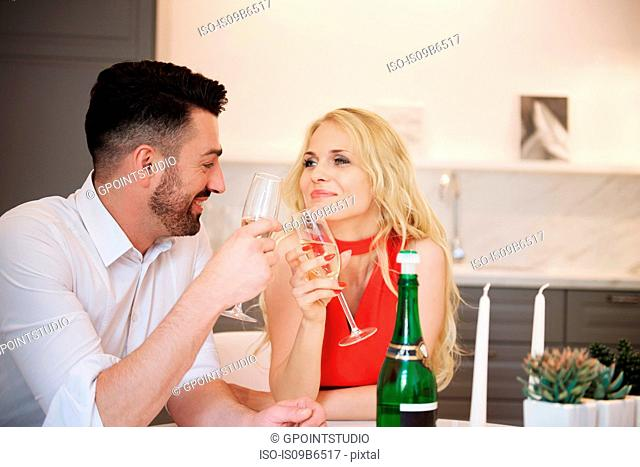 Couple sharing a bottle of champagne, making a toast