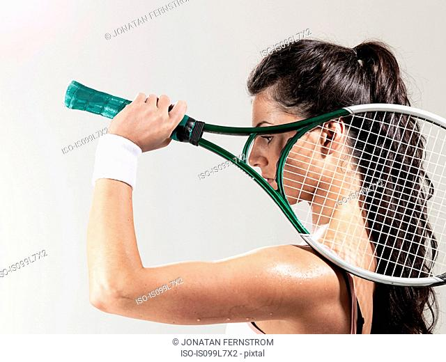 Woman holding tennis racket against white background