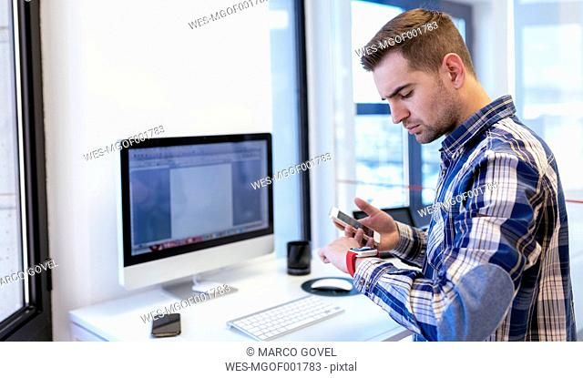 Young man with cell phone and smartwatch in office