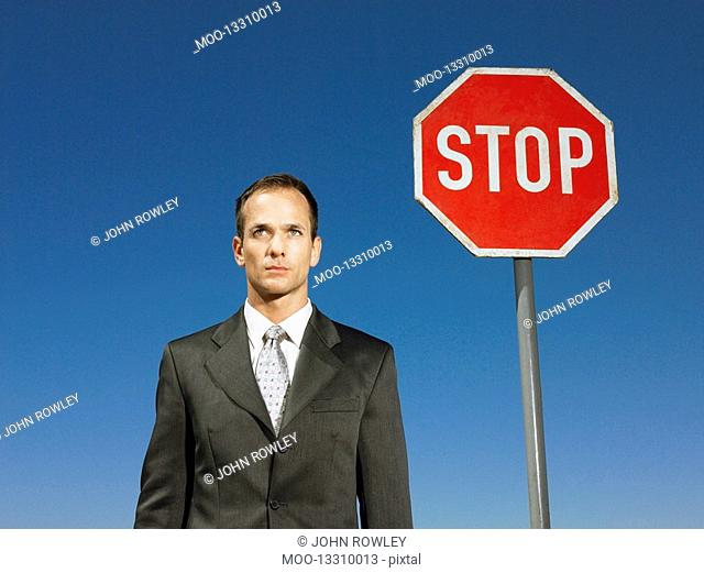 Businessman standing next to stop sign half length