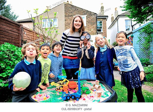Portrait of childminder and children by sandpit looking at camera smiling