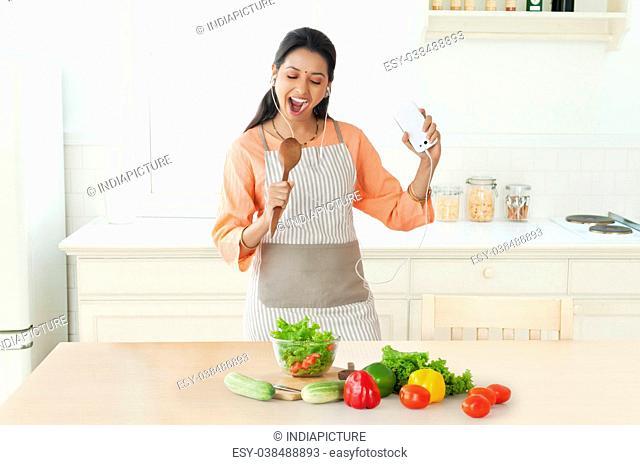 Woman singing in kitchen