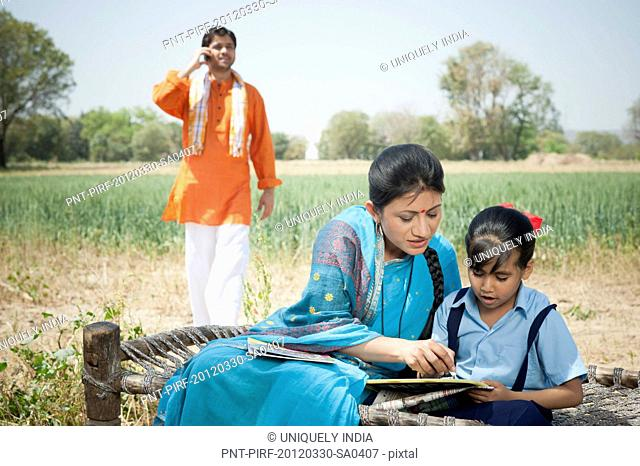 Woman teaching her daughter with her husband talking on a mobile phone, Sohna, Haryana, India