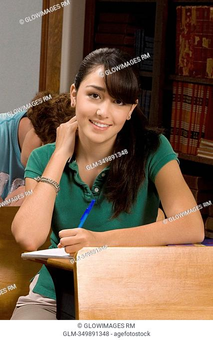 Teenage girl writing in a classroom and smiling