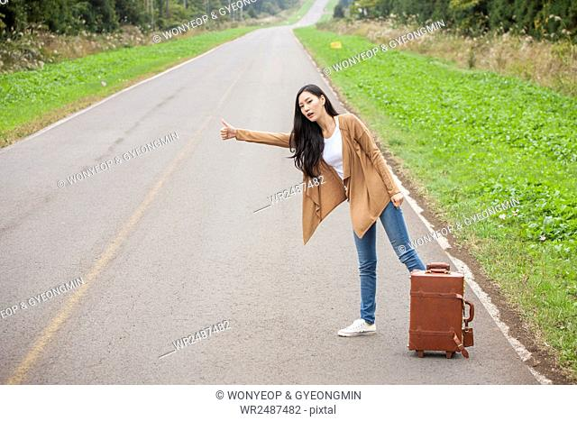 Young female hitchhiker standing at roadside with her carrier
