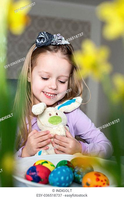 Smiling cute child with easter eggs and plush bunny. Easter, holiday and child concept