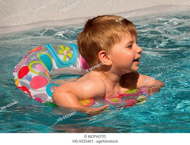 AUSTRIA, LINZ, 29.05.2016, Ein Kind schwimmt mit einem Schwimmreifwn im Pool und kuehlt sich an einem heissen Sommertag ab. - Linz,Austria, 29/05/2016
