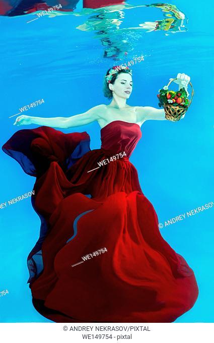 Young beautiful woman in a red dress with a Ñ. posing under water