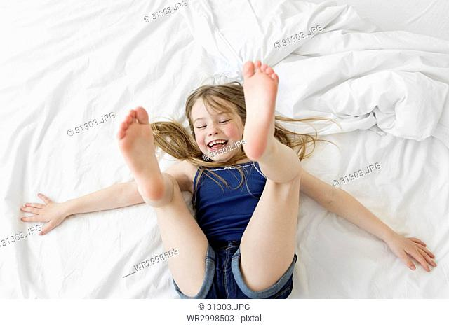 A young girl bouncing on her back on a bed with white sheets