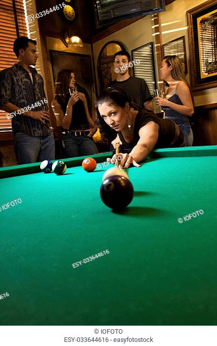 Young caucasian woman preparing to hit pool ball while playing billiards