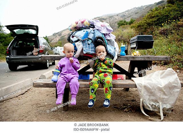 Toddler twins eating banana on picnic bench