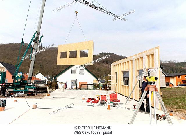 Europe, Germany, Rhineland Palatinate, Man installing and fixing wooden walls of prefabricated house