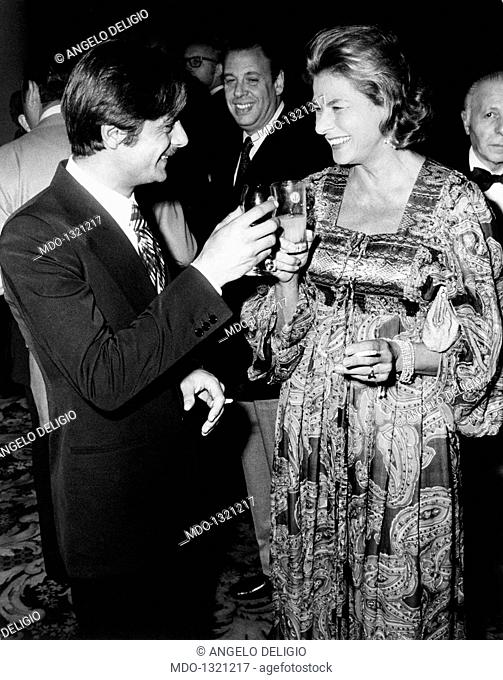 Giancarlo Giannini drinking with Ingrid Bergman at the Cannes Film Festival. The Italian actor and voice actor Giancarlo Giannini touches glasses with the...