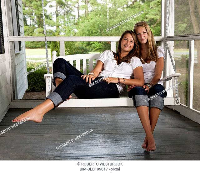 Caucasian sisters sitting on porch swing together