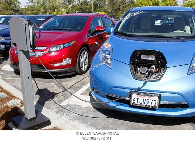 Electric cars plugged into an EV charging station in a workplace parking lot