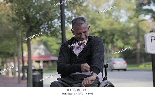 Man with spinal cord injury in a wheelchair putting on his sweater