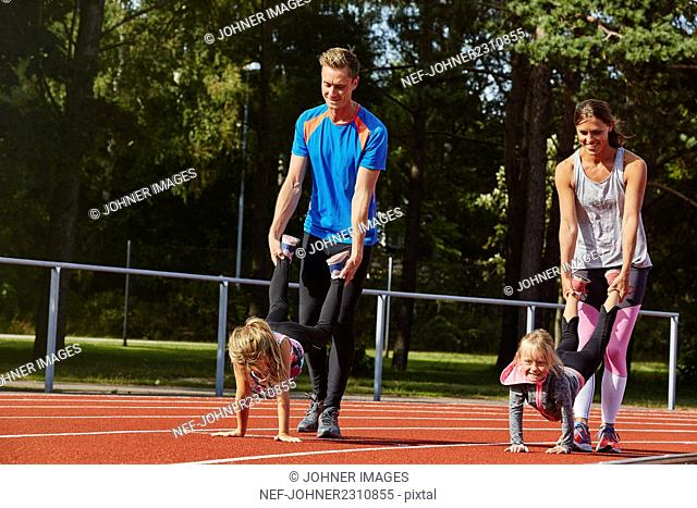Parents with daughters on running track