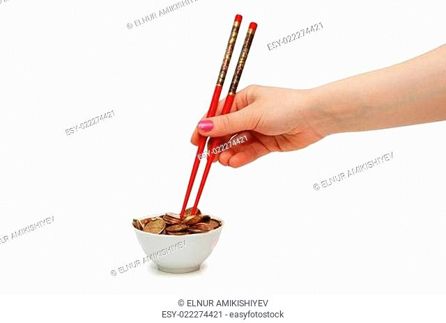 Hand with red chopsticks eating golden coins