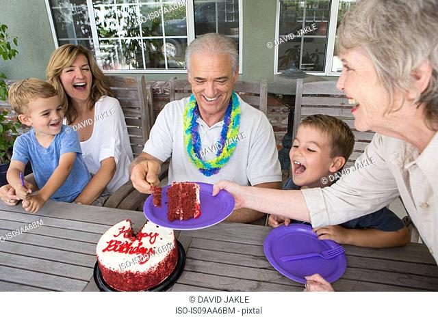 Senior woman serving slice of birthday cake at party with family