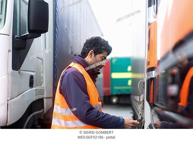 Man wearing reflective vest examining truck