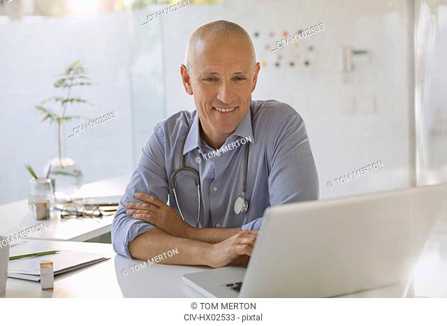 Smiling male doctor working at laptop in doctor's office